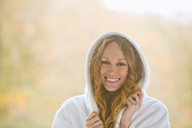 Portrait smiling woman wearing hooded bathrobe - HOXF03129