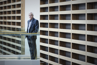 Portrait serious businessman standing on walkway in modern office - HOXF03204
