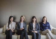Portrait smiling businesswomen sitting in a row on sofa - HOXF03210