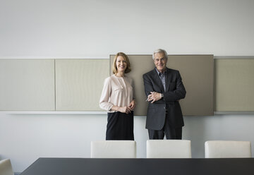 Portrait confident businessman and businesswoman in conference room - HOXF03225