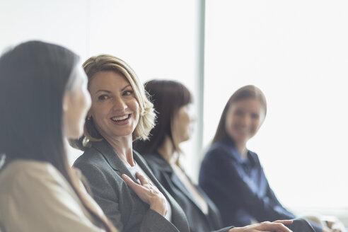 Smiling businesswomen talking - HOXF03237