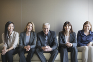 Portrait smiling business people in a row on sofa - HOXF03240