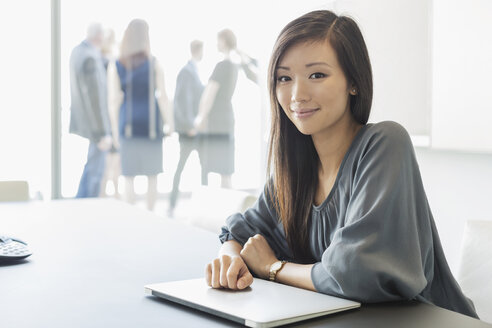 Portrait smiling businesswoman with laptop in conference room - HOXF03243