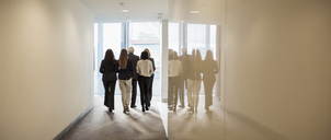 Business people walking in office corridor - HOXF03249
