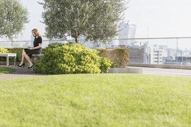 Businesswoman working on urban rooftop garden - HOXF03261