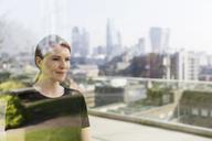 Businesswoman on urban balcony - HOXF03273