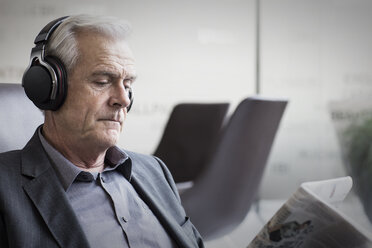Senior businessman with headphones listening to music and reading newspaper - HOXF03276
