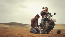 Young couple repairing motorcycle in remote countryside field - HOXF03321