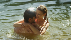 Affectionate couple hugging and swimming in sunny lake - HOXF03327