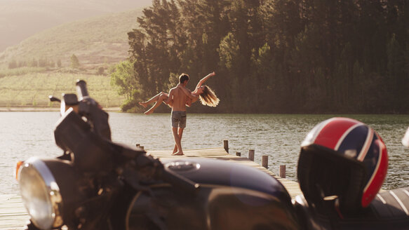 Young man carrying exuberant woman on lakeside dock behind motorcycle - HOXF03333