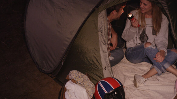Young couple with flashlight inside camping tent - HOXF03342