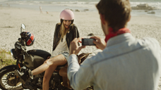 Young man photographing woman on motorcycle at beach - HOXF03345