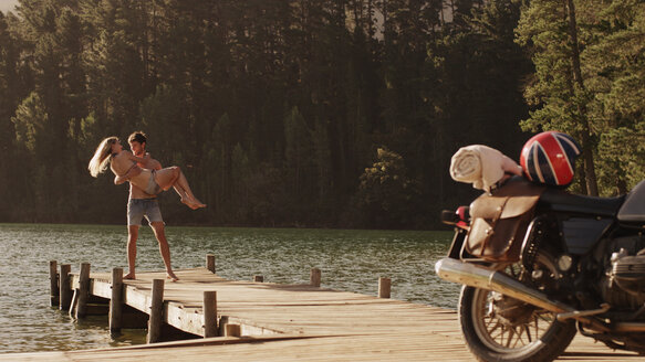 Young man carrying young woman on lakeside dock near motorcycle - HOXF03351