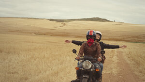 Exuberant young woman riding motorcycle in rural countryside - HOXF03357