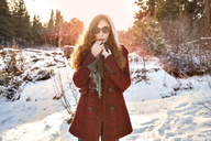 Woman wearing sunglasses standing on snow covered field - CAVF00009