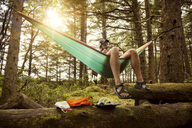 Man relaxing in hammock amidst trees at forest - CAVF00027