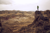 Woman standing on cliff against mountains - CAVF00096
