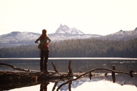 Female hiker standing at lakeshore against mountains - CAVF00123
