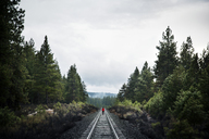 High angle view of woman walking on railroad track at forest - CAVF00138