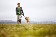 Happy woman walking with dog on grassy field against cloudy sky - CAVF00171