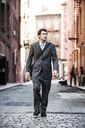 Businessman walking on street amidst buildings - CAVF00201