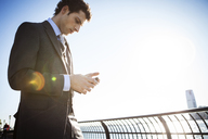 Low angle view of businessman using smart phone against sky on sunny day - CAVF00204