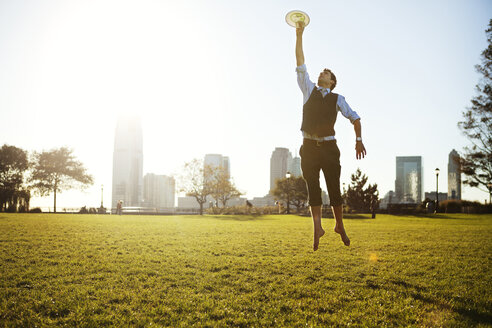 Businessman reaching plastic disk on grassy field against sky - CAVF00213