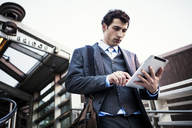 Low angle view of businessman using digital tablet against sky - CAVF00219