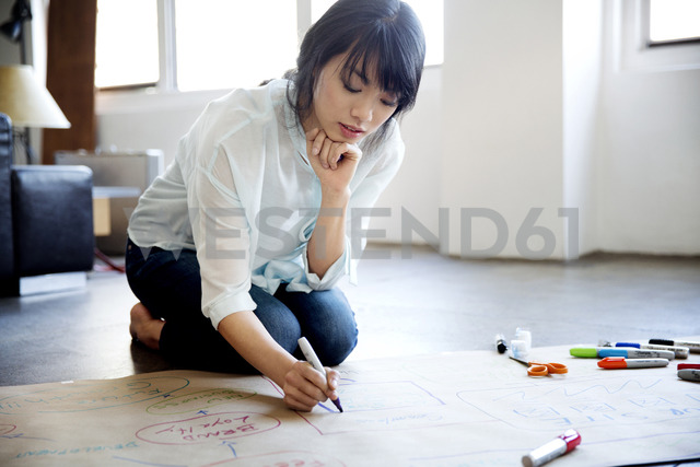 Businesswoman preparing chart in creative office - CAVF00342