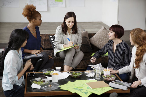 Businesswoman discussing strategy with female colleagues in creative office - CAVF00378