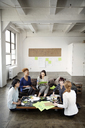 Businesswomen discussing in creative office - CAVF00381