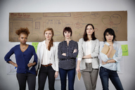 Portrait of confident businesswomen standing in creative office - CAVF00390