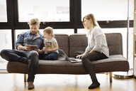 Family using technologies while sitting on sofa at home - CAVF00411