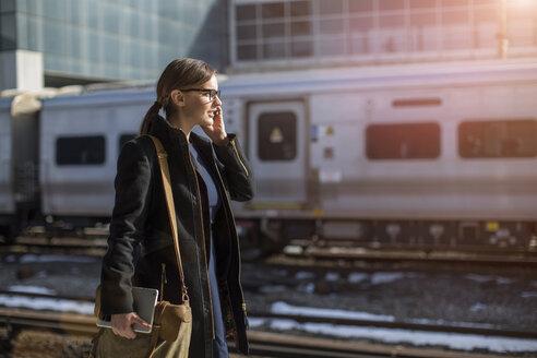 Woman talking on phone while walking at railroad station - CAVF00429