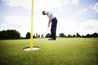 Side view of golfer playing on field - CAVF00657