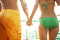 Midsection of young couple holding hands while standing on jetty - CAVF00696