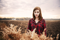 Portrait of beautiful woman standing on field against sky - CAVF00732