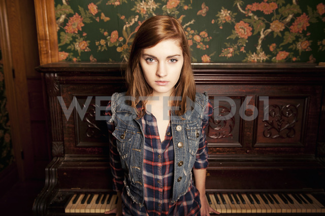 Portrait of young woman standing against piano at home - CAVF00735