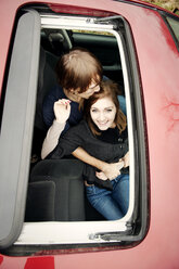 Overhead view of boyfriend kissing happy woman seen through sun roof - CAVF00747