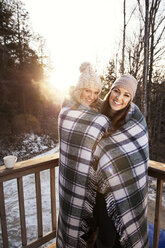 Portrait of happy friends wrapped in blanket standing at patio - CAVF00765