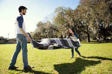 Couple spreading blanket on field at park during sunny day - CAVF00783