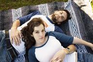 Portrait of couple lying on blanket in park - CAVF00786
