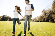 Couple running on grassy field at park during sunny day - CAVF00789