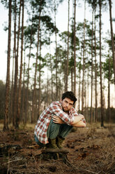 Portrait of man crouching on field in forest - CAVF00792