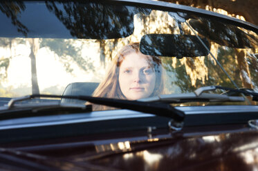 Portrait of woman driving in convertible car seen through windshield - CAVF00807