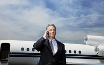 Low angle view of businessman talking on phone while standing against corporate jet on sunny day - CAVF00861