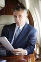 Portrait of confident businessman holding newspaper while traveling in corporate jet - CAVF00864