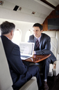 Businessman looking at partner using laptop in corporate jet - CAVF00870