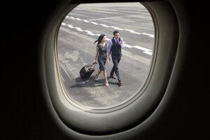Business people walking on runway seen through airplane window - CAVF00876