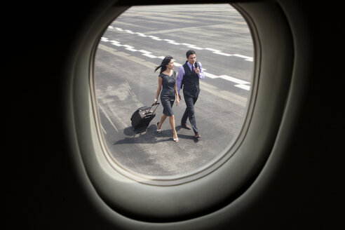 Business people walking on runway seen through airplane window - CAVF00876